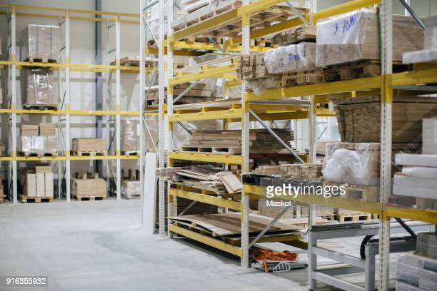 Stack of wooden planks on racks in distribution house