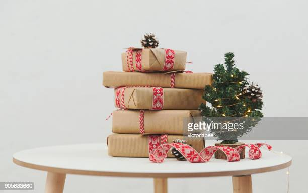 stack of wrapped christmas gifts next to a miniature christmas tree - christmas still life stock pictures, royalty-free photos & images