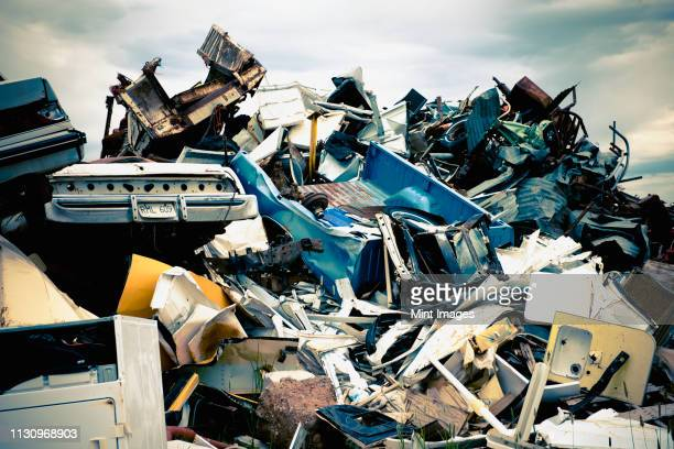 stacked car parts in junkyard - junkyard stock photos and pictures