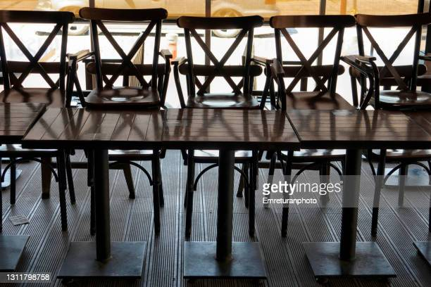 stacked chairs outside the restaurant on a sunny day . - emreturanphoto stock pictures, royalty-free photos & images