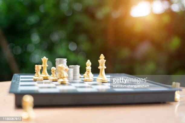 stacked coins on a chess board. conceptual photography on the game in stock market - image - event icon set stock photos and pictures