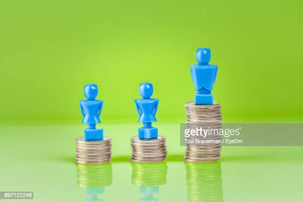 stacked coins with figurines against green background - wage gap stock pictures, royalty-free photos & images
