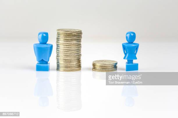 stacked coins with figurines against white background - wage gap stock pictures, royalty-free photos & images