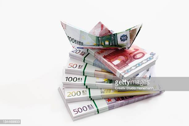 Stacked euro notes in bundles with boat made from notes