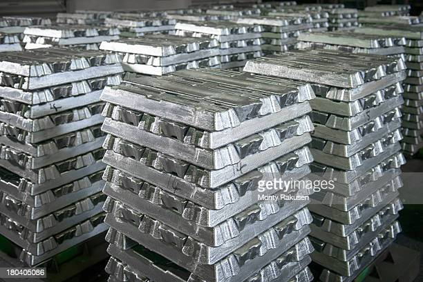 Stacked ingots in aluminium recycling plant warehouse awaiting delivery