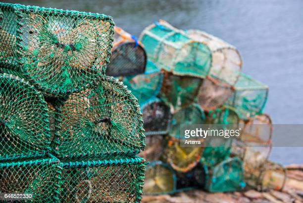 Stacked lobster creels / traps on quay in the Plockton Harbour Scottish Highlands Scotland UK