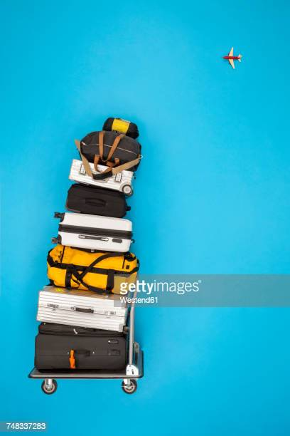 Stacked luggage and plane flying in the sky