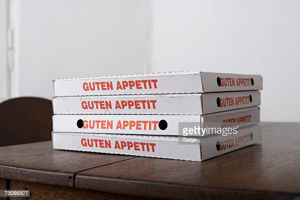 Stacked pizza boxes on table