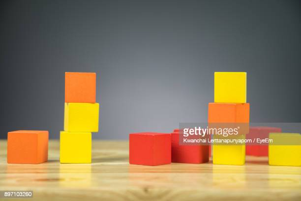 Stacked Red And Yellow Toy Blocks On Table Against Gray Background