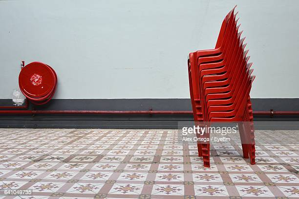 Stacked Red Chairs On Tiled Floor
