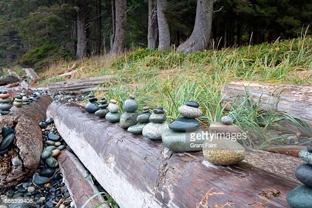 Stacked rocks on log.