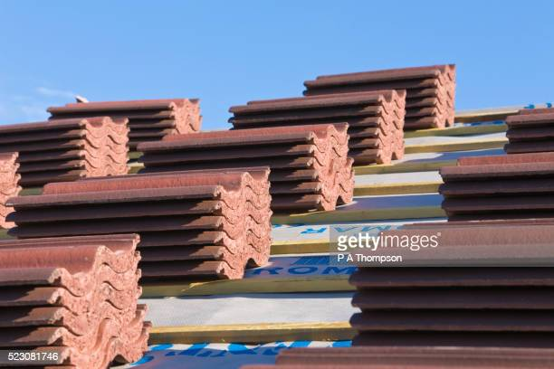 stacked roof tiles on roof of new house - tetto foto e immagini stock