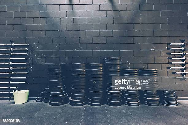 stacked rows of barbell weights in black gym - leisure facilities stock pictures, royalty-free photos & images