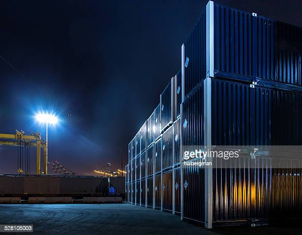 stacked shipping containers in dockyard at night - commercial dock stock pictures, royalty-free photos & images