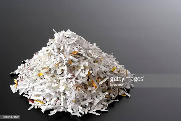 Stacked shredded documents on black desk