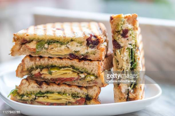 stacked vegetarian sandwiches of arugula, artichoke, sun dried tomato, pesto - sandwich stock pictures, royalty-free photos & images