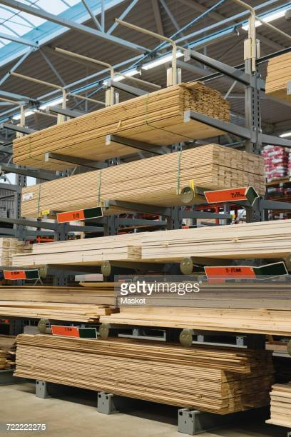 Stacked wooden planks arranged on shelves in hardware store warehouse