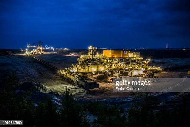 A stacker and a station conveying overburden are pictured at the lignite mine WelzowSued during blue hour on August 15 2018 in Neupetershain Germany