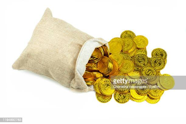 stacking gold coin in treasure sack on white background - cyst stock pictures, royalty-free photos & images