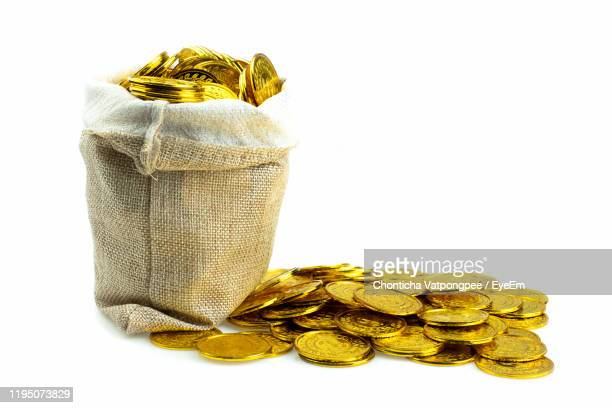 stacking gold coin in treasure sack on white background - sac stock pictures, royalty-free photos & images