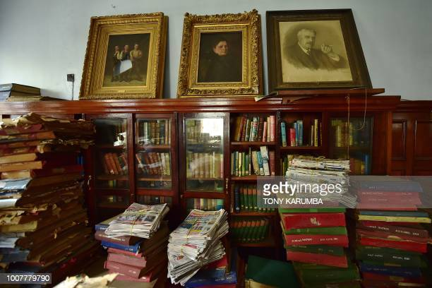 Stacks of binders used to archive newspapers rise from the floor of an upper room bearing victorian period paintings of unidentified individuals...