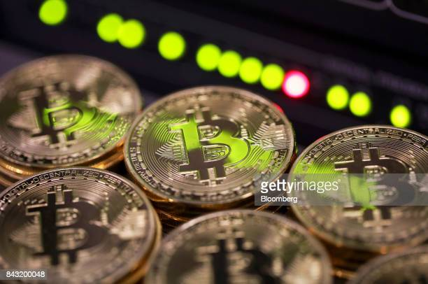 Stacks of bitcoins sit near green lights on a data cable terminal inside a communications room at an office in this arranged photograph in London UK...