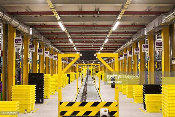 Stacks of crates stand at either side of a conveyor in a picking tower at the Amazoncom Inc fulfillment center in Poznan Poland on Friday June 12...