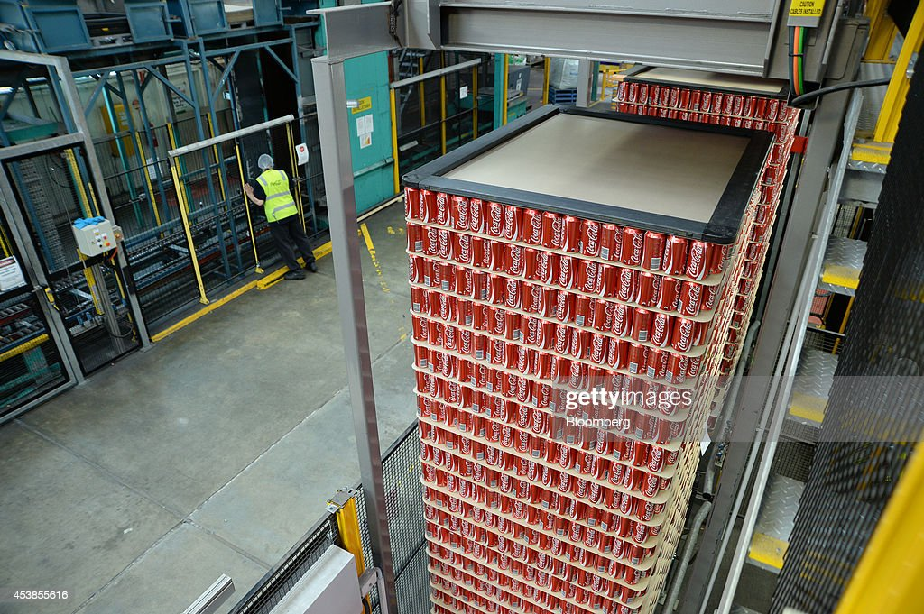 Stacks of empty Coca-Cola Classic cans move along a conveyor towards the filling area at a Coca-Cola Amatil Ltd. production facility in Melbourne, Australia, on Tuesday, Aug. 19, 2014. Coca-Cola Amatil flagged a second consecutive drop in full-year earnings amid weak consumer confidence and rising costs in Indonesia. Photographer: Carla Gottgens/Bloomberg via Getty Images