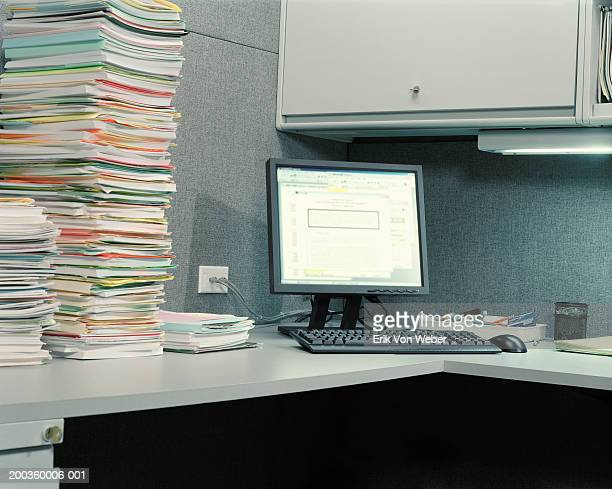 Stacks of file folders on desk, next to desktop computer