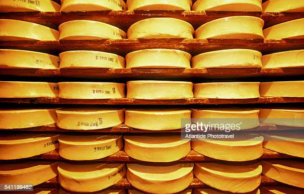 stacks of fontina cheese on shelves - クールマイヨール ストックフォトと画像