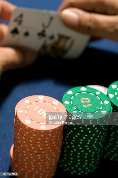 Stacks of gambling chips next to hand holding playing cards