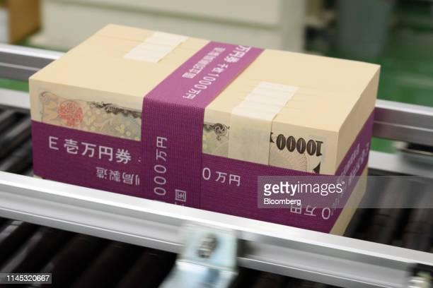 Stacks of Japanese 10000 yen banknotes move along a conveyor at the National Printing Bureau Tokyo plant in Tokyo Japan on Monday May 20 2019 Japans...