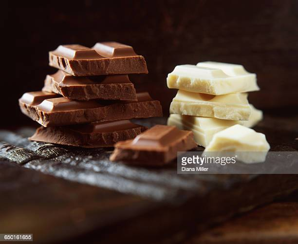 Stacks of milk and white chocolate on wooden cutting board