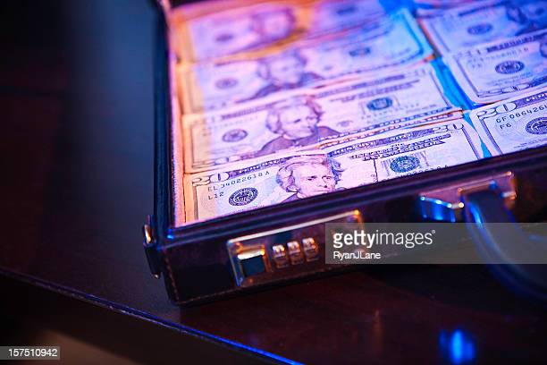 stacks of money in a briefcase - money laundering stock photos and pictures
