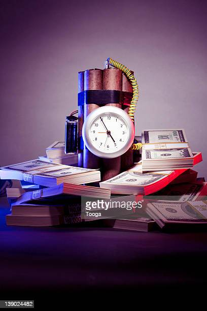 stacks of money with time bomb - time bomb stock photos and pictures
