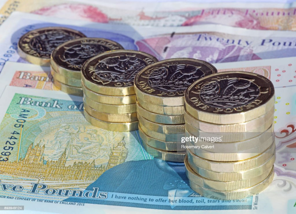 Stacks of one pound coins on British pound notes. : Stock Photo