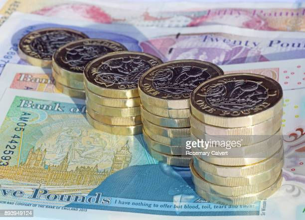 stacks of one pound coins on british pound notes. - british pound sterling note stock pictures, royalty-free photos & images