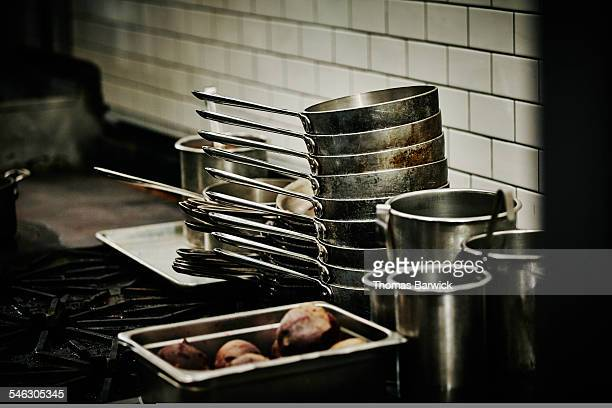 Stacks of pots on range in restaurant kitchen