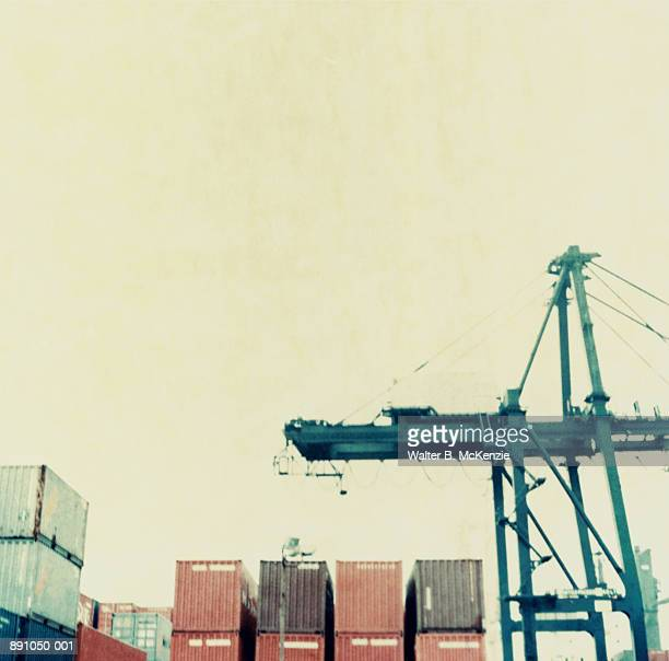 Stacks of shipping containers and crane on dock (paper negative)