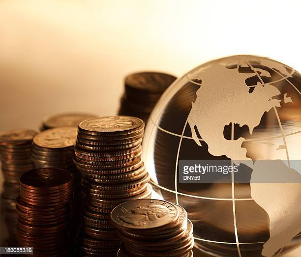 Stacks of U.S. coins next to globe showing North America