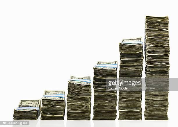 stacks of us currency in ascending graph pattern - dinero fotografías e imágenes de stock