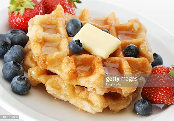 Stacks of waffles surrounded with berries, syrup and butter