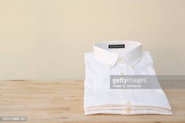 stacks of white shirts - white shirt stock pictures, royalty-free photos & images