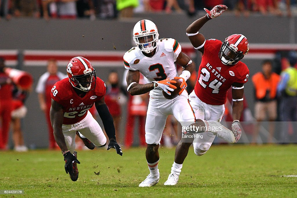 Stacy Coley #3 of the Miami Hurricanes catches a 51-yard pass against Jack Tocho #29 and Shawn Boone #24 of the North Carolina State Wolfpack at Carter-Finley Stadium on November 19, 2016 in Raleigh, North Carolina. Miami won 27-13.