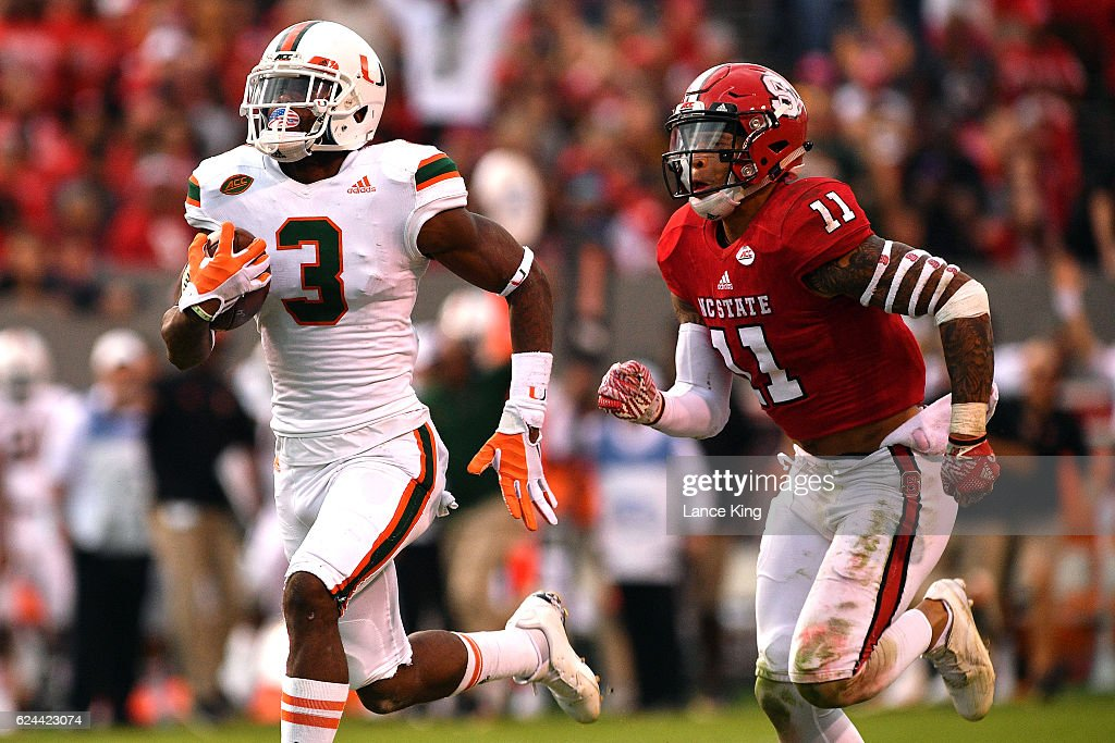 Stacy Coley #3 of the Miami Hurricanes runs during his 51-yard pass catch against Josh Jones #11 of the North Carolina State Wolfpack at Carter-Finley Stadium on November 19, 2016 in Raleigh, North Carolina. Miami won 27-13.