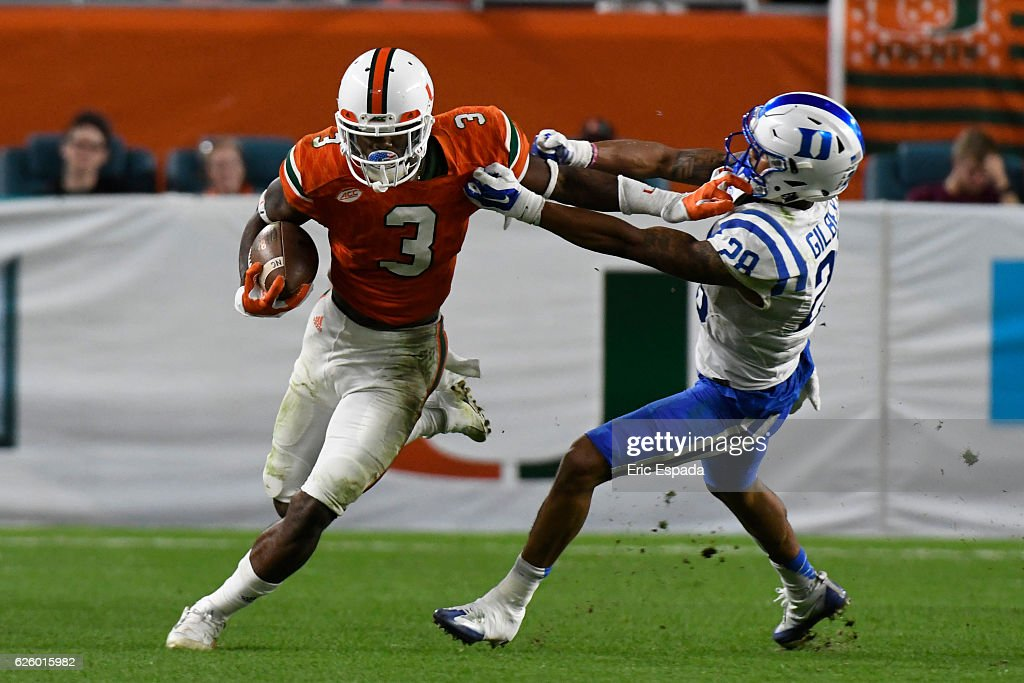 Stacy Coley #3 of the Miami Hurricanes stiff arms Mark Gilbert #28 of the Duke Blue Devils during the 4th quarter of the game at Hard Rock Stadium on November 26, 2016 in Miami Gardens, Florida.
