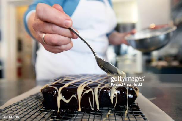 Stacy Cooper puts an Irish Cream Drizzle made with confectioners sugar and Irish Cream liqueur on the beer brownies at Biscuits and Company in...