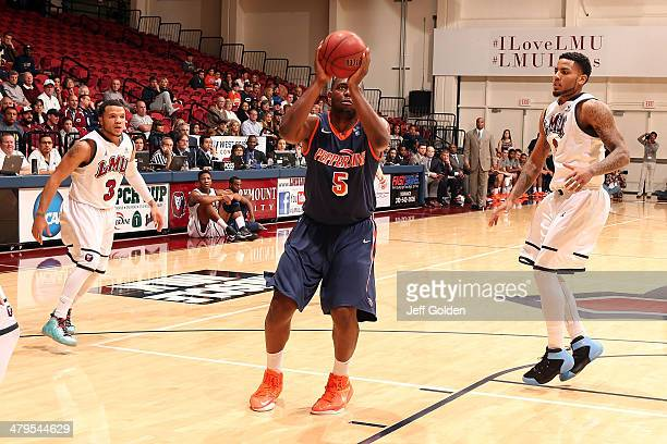 Stacy Davis of the Pepperdine Waves shoots a jump shot against Anthony Ireland and CJ Blackwell of the Loyola Marymount Lions in the first half of...