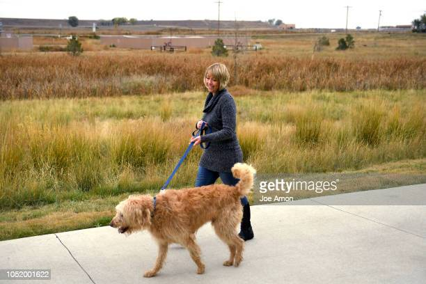 Stacy Lambright with her goldendoodle Teddy along the South Fork Preble Creek Trail near her home in North Creek Farms The trail is close by the well...
