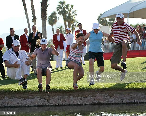 Stacy Lewis caddie Travis Wilson sister Janet Lewis mother Carol Lewis and father Dale Lewis take the traditional jump into the pond after Lewis won...